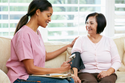caregiver monitoring elderly woman's blood pressure