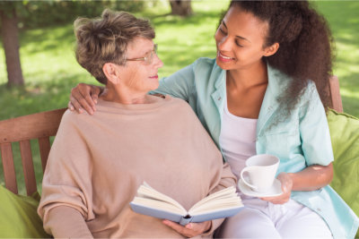 elderly woman having conversation with her caregiver